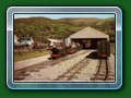 1957: 'Count Louis' with ex-Hardwick twin-bogie wooden-bodied carriages & the half+half carriage at the rear waits to leave the new Fairbourne terminus, postacrd - Bill Hyde collection